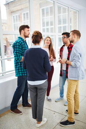 ethnicity: Guys and girls communicating in college corridor