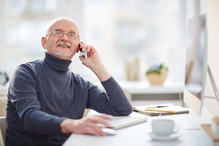 Mature man sitting by computer and speaking on cellphone