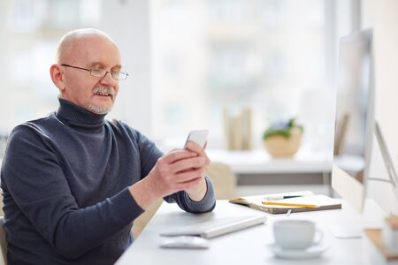 work addicted: Mature man with cellphone sitting by computer in office