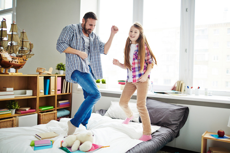 Happy girl and her father dancing on bed Stockfoto