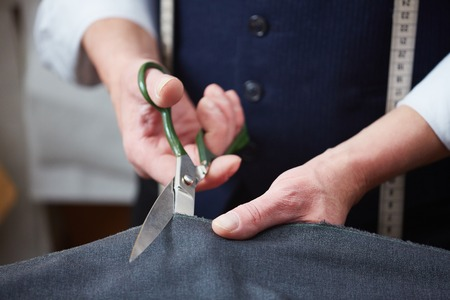 scissors: Hands of tailor with scissors cutting fabric Stock Photo