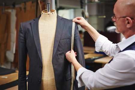tailor measuring tape: Tailor with measuring tape taking measures of jacket on mannequin