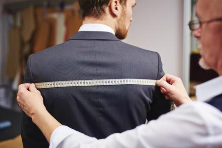 Dojrzałe Krawiec pomiaru tył kurtki noszone przez jego klienta