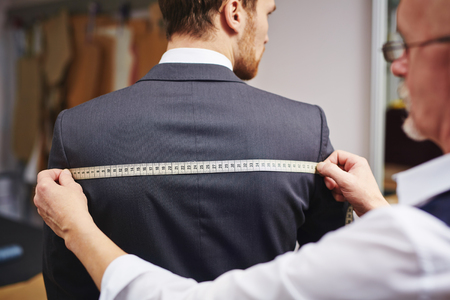 tailor shop: Mature tailor measuring back of jacket worn by his client