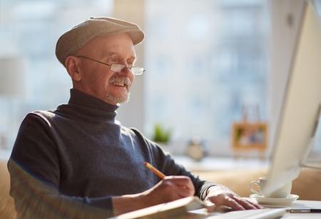 hombre escribiendo: Viejo sonriente de trabajo con ordenador Foto de archivo