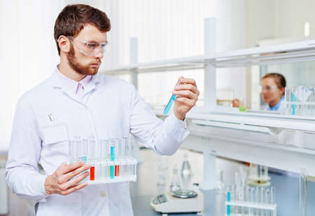 protective eyewear: Confident young man in protective eyewear holding test tube with blue liquid