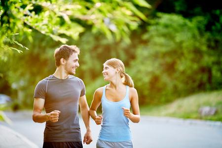 Pareja joven corriendo juntos en día de verano