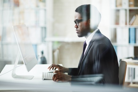 business manager: Businessman sitting at his workplace and using computer