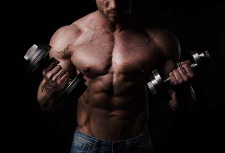 body torso: Handsome athletic man bodybuilder doing exercises with dumbbells Stock Photo