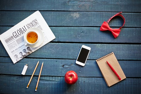 tea table: Newspaper, cup of tea and cellphone on wooden table