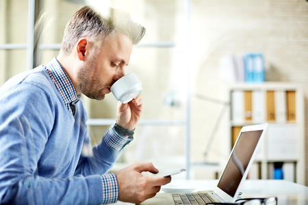 work addicted: Modern businessman drinking tea and reading sms in office