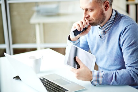technology career: Modern businessman with touchpad and cellphone sitting at workplace in front of laptop
