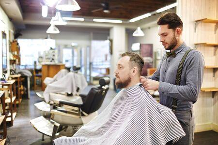 barbershop: Contemporary young man visiting barbershop Stock Photo