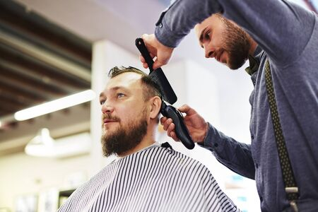 haircutting: Modern barber with haircutting tools serving his client Stock Photo