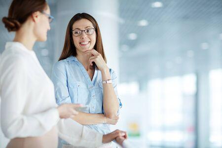 Cheerful businesswoman écouter son collègue