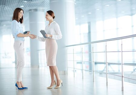Young businesswomen greeting one another