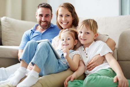 familias felices: familia joven mirando a la cámara en casa