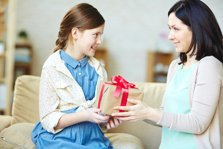 Mother giving package with gift to her daughter