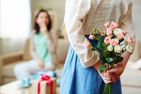 Girl holding bunch of roses for her mother behind back Stock Photo