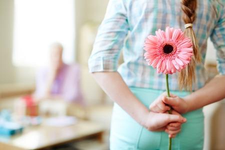 彼女の後ろにピンクのガーベラを隠す女の子