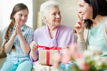 youth group: Elderly woman unwrapping package between her daughter and granddaughter