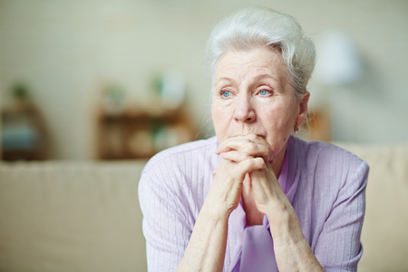 Elderly woman keeping hands by her lips