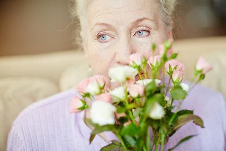 smelling: Elderly woman smelling fresh roses