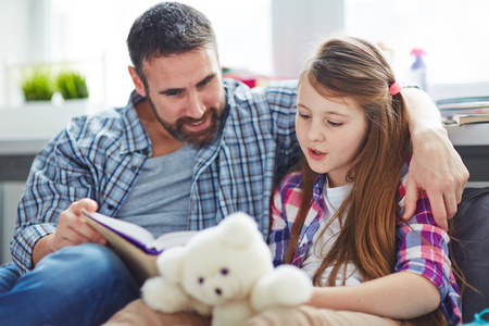 person reading: Teenage girl reading aloud with her father near by Stock Photo