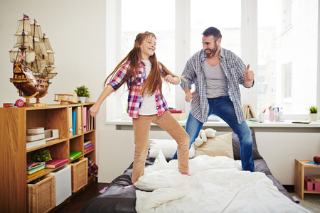 Cheerful girl and her father dancing on bed and having fun