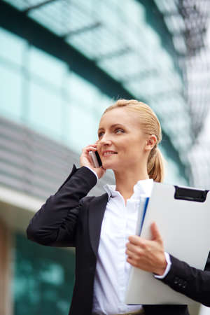 modern businesswoman: Successful young businesswoman with cellphone calling by modern building