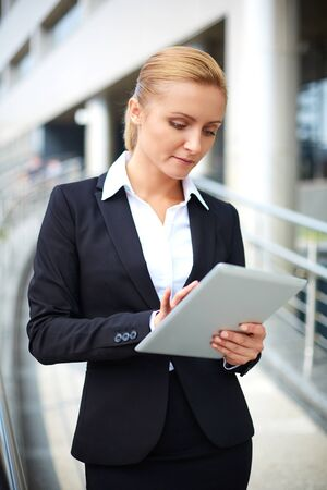 work addicted: Modern young businesswoman using touchpad outside