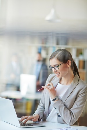 professional woman: Young businesswoman typing at workplace in office Stock Photo