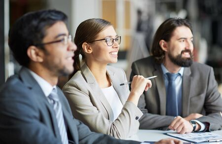 man studying: Smiling businesswoman listening to speaker between her two colleagues at seminar Stock Photo
