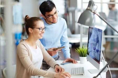 monitor de computadora: La sonrisa de negocios y su colega mirando el monitor del ordenador en la oficina