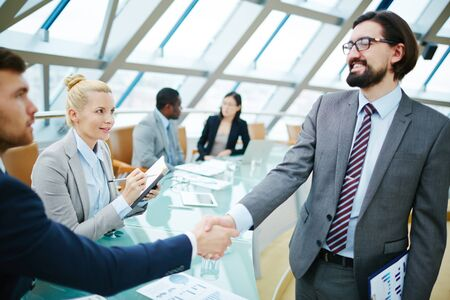 handshaking: Young secretary looking at businessmen handshaking after introduction Stock Photo