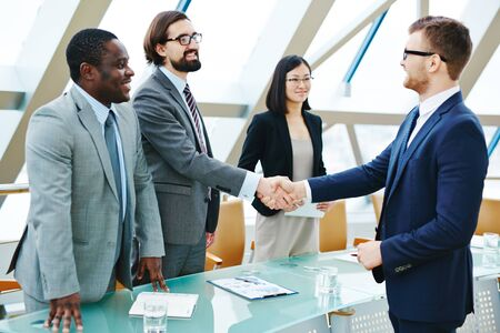 handshaking: Young businessmen handshaking at meeting after signing contract