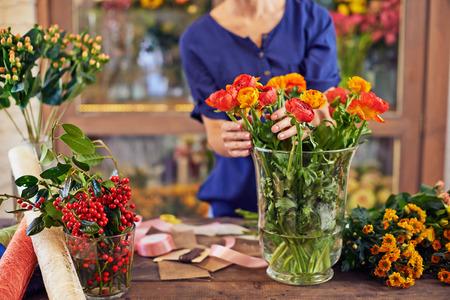 flower seller: Flower seller selecting flowers from glass vase