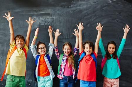 Joyful pupils with backpacks raising hands while standing against blackboard