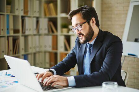 busy beard: Asian businessman in formalwear networking in office Stock Photo