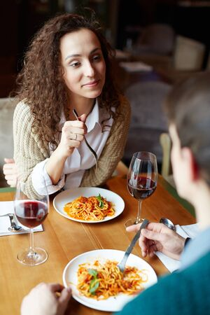 woman eating: Amorous couple eating spaghetti and drinking red wine in restaurant Stock Photo