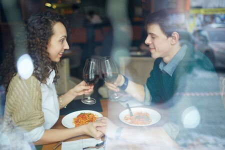 toasting: Amorous couple toasting with red wine in Italian restaurant