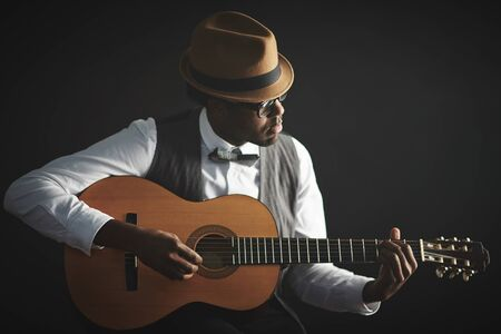 African man playing guitar isolated on black background Stock Photo