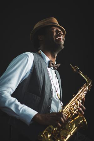 Saxophonist playing saxophone on black background