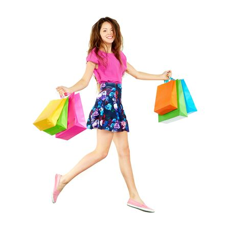 paperbags: Pretty shopper carrying paperbags and looking at camera with smile