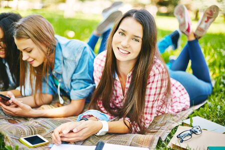 girl lying: College student looking at camera while relaxing outdoors with her friends near by Stock Photo