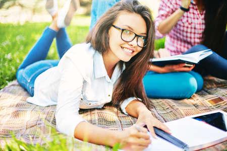 belle brune: Une adolescente en regardant la caméra tout en faisant des notes en plein air avec ses amis sur le fond