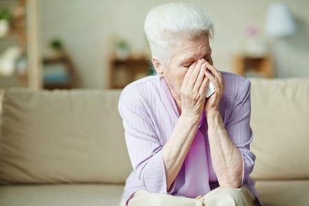 Ongelukkig senior vrouw huilen op de bank
