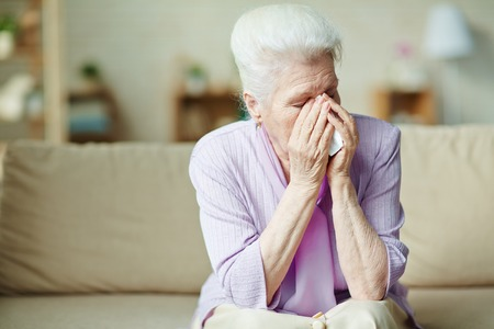 Unhappy senior woman crying on sofa