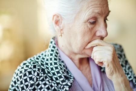 Nadenkend senior vrouw met haar hand op de mond Stockfoto