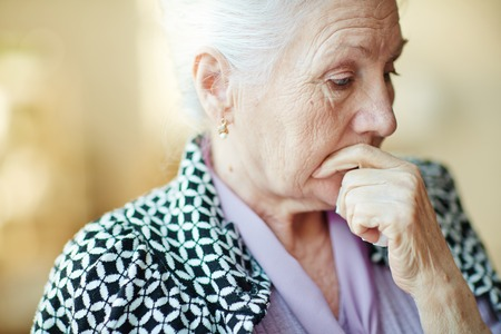 Pensive senior woman with her hand by mouth